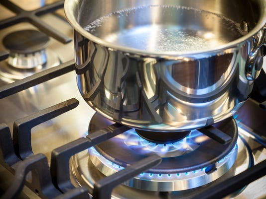 Pot on stove with gas burner and flame