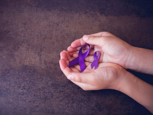 hands holding Purple ribbons,toning copy space background, Alzheimer's disease, Pancreatic cancer, Epilepsy awareness, Hodgkin's Lymphoma awareness