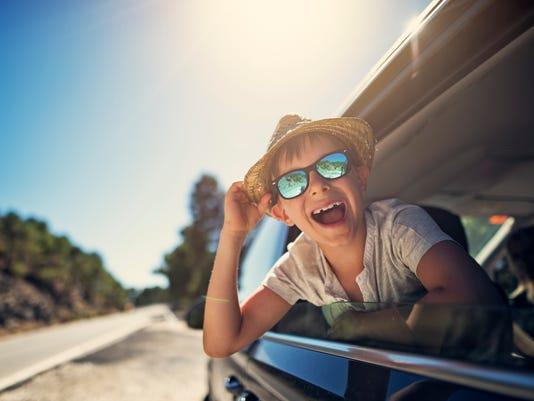 Happy little boy enjoying road trip