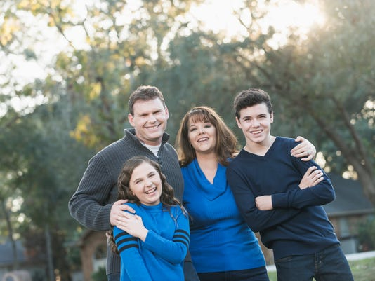 Family of four standing in front yard