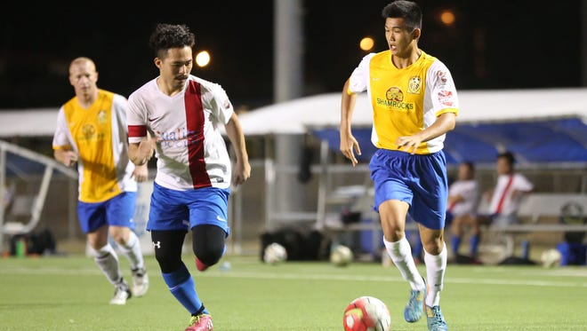 The Rovers FC DI's Takumi Ito looks to send a cross to a teammate facing defensive pressure from Quality Distributors FC's RC Salas during a final week match of the Budweiser Soccer League Premier Division Sunday at the Guam Football Association National Training Center. The Rovers FC DI won 10-1.