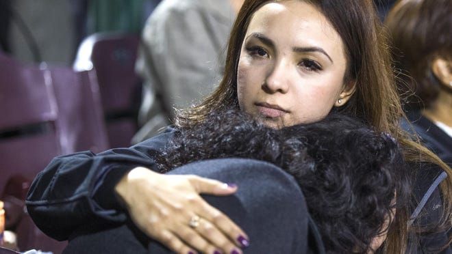 Michelle Zamora , left, is comforted by her sister, Melissa Zamora, of San Bernardino, at a vigil at San Manuel Stadium Thursday night, December 3, 2015, in remembrance of the 14 people lost Wednesday in the San Bernardino mass shooting.