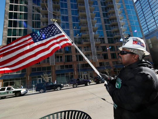 Emmett Cromwell waves an American flag during the announcement that more than 150 workers who helped install drywall in a new luxury high-rise, which stands in the background, will be able to share in a settlement of over $800,000 in a class action lawsuit over unpaid wages during a news conference in downtown Denver Wednesday, Dec. 20, 2017. Under the terms of the deal for the nine workers who filed the case, workers who installed drywall and others who cleaned up and hauled debris from the SkyHouse Denver between September 2015 and July 2016 will be eligible to get about $200 for every week that they worked on the project. (AP Photo/David Zalubowski)