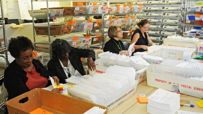 File- Brevard County elections workers prepare absentee ballots to send in the mail.