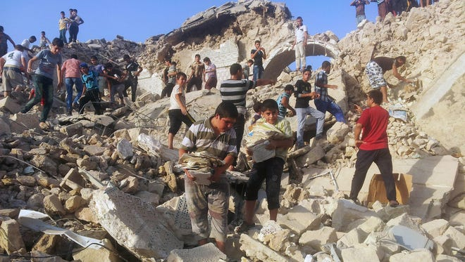 People pick through the rubble of the destroyed Mosque of The Prophet Younis, or Jonah, in Mosul, Iraq