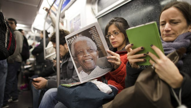 FILE - In this Dec. 6, 2013, file photo, a subway rider in New York reads a newspaper featuring news of the death of South African leader Nelson Mandela.