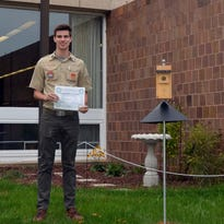 Alex M. Dunbar of Montgomery holding the commendation letter from Somerset County Library Commission that he received after completing his Eagle Scout perennial garden project.