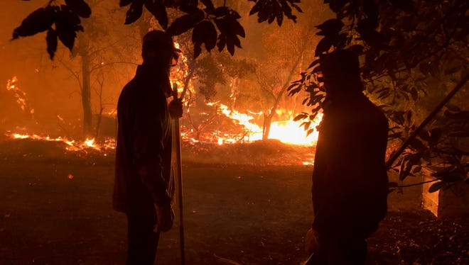 Rio Mesa High graduate and IndyCar driver Charlie Kimball, left, and his father Gordon help fight the Thomas Fire as it burns through the family's avocado ranch in December. The ranch was nearly completely destroyed.