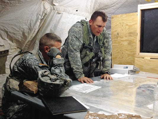 Lt. Col. Mark Hoovestol, right, gets some mentoring from an observer-coach-trainer at the National Training Center at Fort Irwin, Calif.
