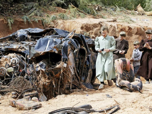 People walk pass a severely damage vehicle swept away by a surge of water during a flood Tuesday, Sept. 15, 2015, in Hildale, Utah. The floodwater swept away multiple vehicles in the Utah-Arizona border town, killing several people. (AP Photo/Rick Bowmer)