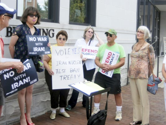 From left, Russell Martz, Bob Logan (partially hidden), Sharon Kelly, Natalie Winter, Michele Epps, Lance Lessler, Kathleen Kaminski and Alanna Hartzok participate in a protest outside the Chambersburg office of U.S. Rep. Bill Shuster on Wednesday. They are members of the group MoveOn.org, and were protesting the congressman's opposition to the Iran nuclear deal.