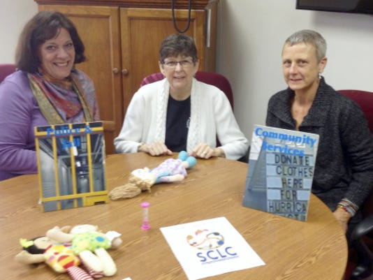 Kim Kreider-Umble, from left, of Lebanon Family Health Services; Sally Smedley, COPE volunteer; and Laurie Funk of Youth for Christ;look over props used in the Cost of Poverty Experience.