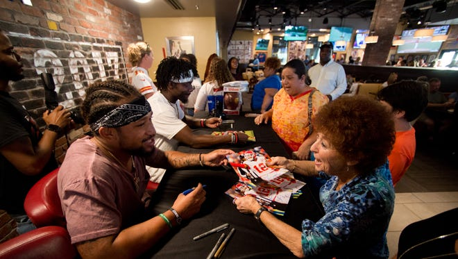 "Kansas City Chiefs wide receiver Albert Wilson (left), a former Port St. Lucie High School football star, talks with Arlene Klein, of Tradition, after signing photographs for her during a meet-and-greet event Friday, June 23, 2017, at Recovery Sports Grill in Tradition. ""They're big football fans,"" Klein said about her son and grandson, to whom she planned to send the autographs. ""They'll be thrilled, they really will."" Wilson's former teammate Frankie Hammond (center), now with the New York Jets, also was there to sign photos and pose with fans before the Albert Wilson Foundation events this weekend."