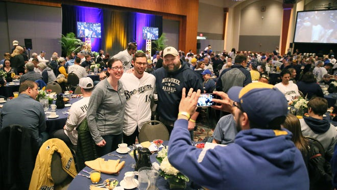 Brewers second baseman Eric Sogard poses for pictures as he has breakfast with fans including Amy Karn (left) and Aaron Karn of Omro.