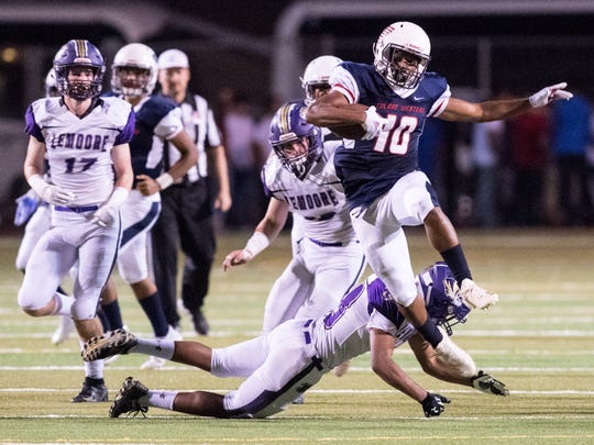 Tulare Western's Andrew Davis leaps over a defender against Lemoore in a non-league high school football game on Thursday, August 30, 2018.