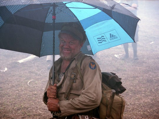 John C. Reilly poses goofily with an umbrella while