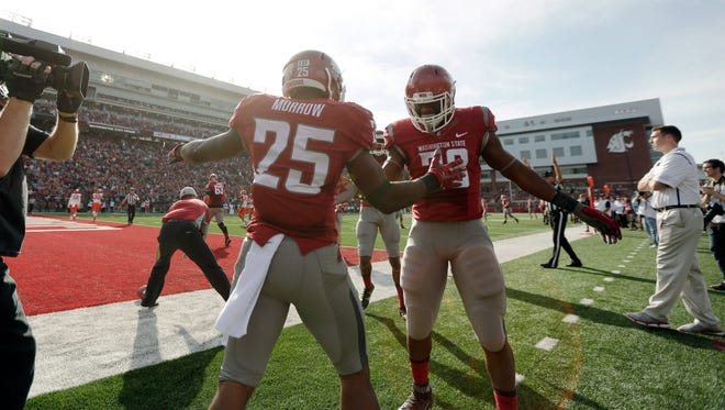 After running in for a touchdown, Washington State running back Jamal Morrow (25) celebrates with teammate running back Gerard Wicks (23) during the first half of an NCAA college football game against Oregon State, Saturday, Oct. 17, 2015, in Pullman, Wash.