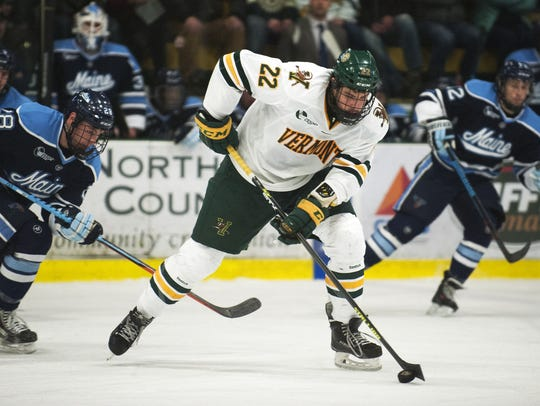 Catamounts forward Brady Shaw (22) plays the puck during