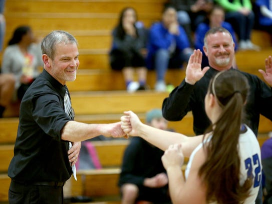Olympic coach Bryan Hanley fist-bumps player Emma Meadows during introductions before a recent game. Hanley takes over a team that has most of its key contributors back from a Class 2A state tournament qualifier last year.