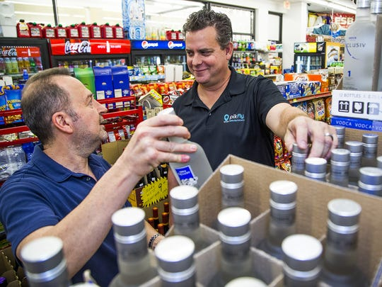Maryland Deli & Liquor owner Nick Hanna, left, talks