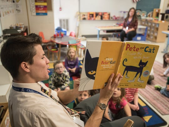 Allen Elementary preschool teacher Kris Wiseman reads to his students while wearing his signature Wednesday Elvis Presley tie earlier this year.