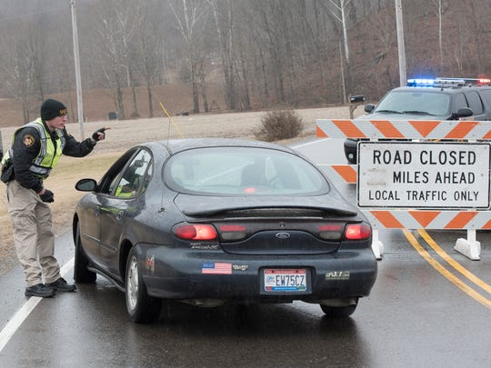A Deputy Sheriff redirects traffic for those wanting to go to the library located beside the scene of the shooting Thursday morning on Ohio 124.