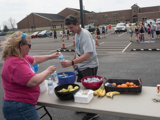 Volunteer Leona Weaver passes out water to runners at Southeastern Local Schools after they finish their leg of the race.
