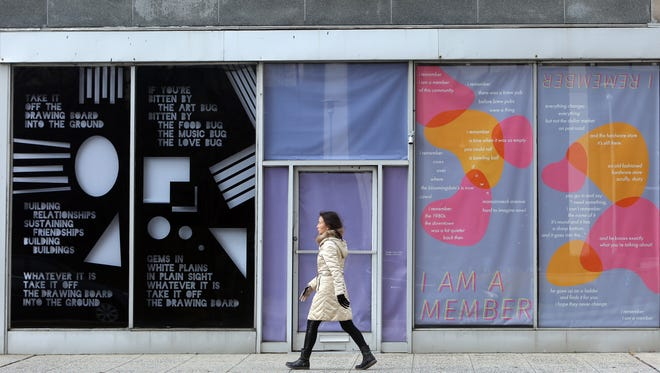 A woman walks by some of the vacant store front windows on East Post Road in  White Plains in White Plains where SUNY design students have placed art work.
