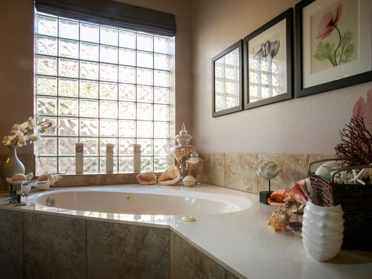 A large glass-block window softens the natural light entering the master bathroom. Detail of the master bathroom of the North Scottsdale remodeled home of Barbara and Joe Byrne.