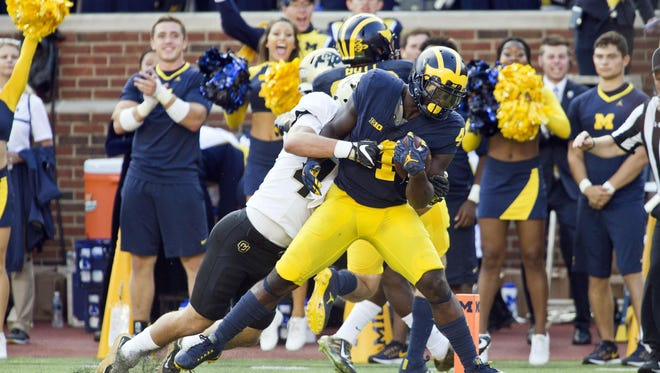 Michigan running back De'Veon Smith scores a touchdown, dragging Colorado's Christian Shaver with him into the end zone after a 42-yard run.