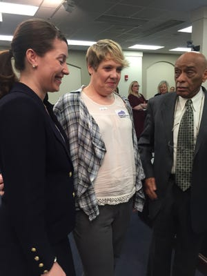 Rebecca Collett (center) talked with supporters of the expungement bill, Rep. Darryl Owens, left, and Alison  Lundergan Grimes, Kentucky secretary of state.