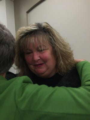 Kelly Gunning of Lexington was embraced by a well-wisher after she testified about potential budget cuts to human services.