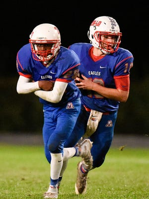 St. Cloud Apollo quarterback Joey Atkinson, right, keeps the ball on a fake handoff to Schanonn Spears Jr. against Moorhead during the second half Friday at Apollo High School in St. Cloud.