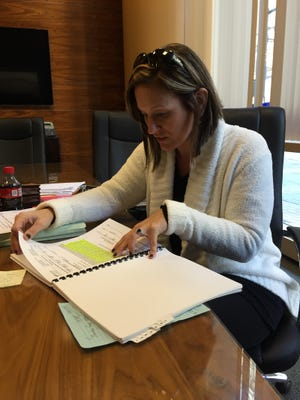 Julie Locke looks through records from her custody case in which a finding of child neglect against her ex-husband was reversed.