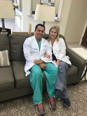 Dr. Alvernia and his wife Courtney in their Monroe clinic.