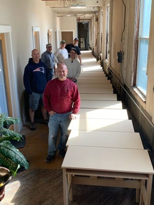 """From front to back, """"Keep the Kids Focused"""" volunteers Chris Pandiscio, Dan Doiron, Nicole Paré, Bob Marchetti, Bob Antocci and Jason Paré with some of the desks they have made."""