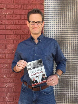 """History professor Landry Brewer holds his new book, """"Cold War Kansas."""" Among the cities featured is Dodge City."""