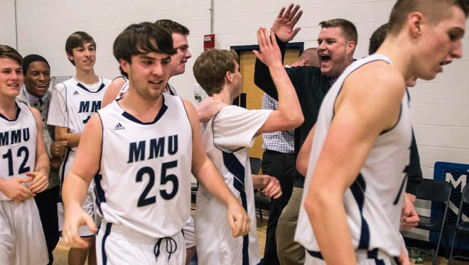 MMU coach  Jess Davis high-fives Trent LaBounty following a dramatic win over St. Johnsbury last season. Monday, LaBounty and MMU nipped Rice 64-62.
