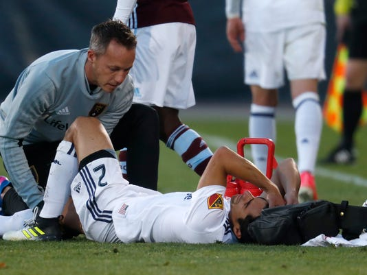 Real Salt Lake defender Tony Beltran, right, rects as he is attended to by a trainer after being injured against the Colorado Rapids in the first half of an MLS soccer match, Sunday, Oct. 15, 2017, in Commerce City, Colo. (AP Photo/David Zalubowski)