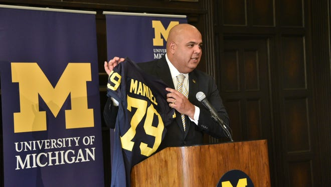 New Michigan athletic director Warde Manuel holds up a Wolverines jersey at Friday's news conference.