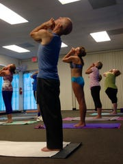 Participants in a 90-minute hot yoga class at the Inverted Elephant in Titusville move through a breathing and stretching exercise.