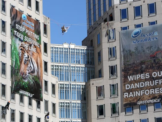 Nine Greenpeace activists rappel and hang banners in protest of Procter & Gamble outside of the company's headquarters.