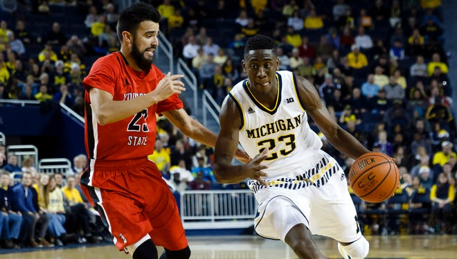 Michigan guard Caris LeVert (23) moves the ball defended by Youngstown State guard Francisco Santiago (23) in the first half of U-M's 105-46 win Saturday at Crisler Center.