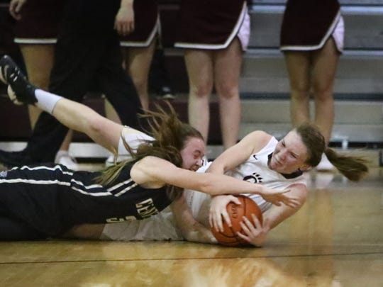 Central Magnet's Sydney Smith and Cannon County's Maleah Scott fight for a loose ball.