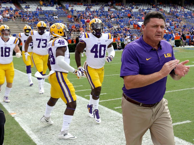 LSU head coach Ed Orgeron takes the field with players