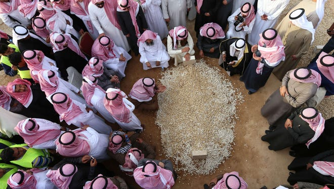 Mourners gather around the grave of Saudi Arabia's King Abdullah at the Al-Oud cemetary in Riyadh on Jan. 23, 2015, following his death in the early hours of the morning. Foreign leaders gathered in the Saudi capital for the funeral of the ruler of the world's top oil exporter and the spiritual home of Islam.