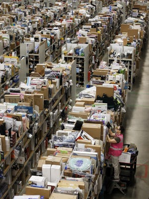 A worker fills orders at the Amazon fulfillment center in Lebanon, Tenn. on Monday, Dec. 1, 2014.