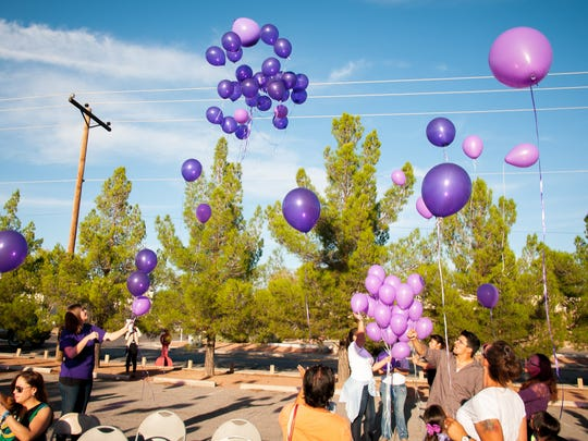 Balloons are released at the parking lot of safe housing and counseling center La Casa on Thursday as part of a vigil to honor victims of domestic violence.
