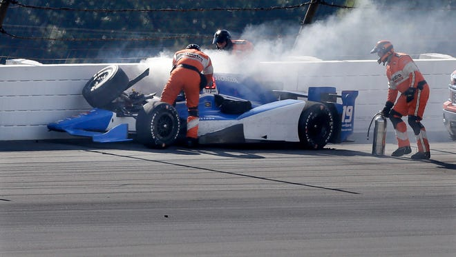 Rescue personnel assist Tristan Vautier, of France, after he collided with Graham Rahal and hit the wall in Turn 3 after colliding during the Pocono IndyCar 500 auto race Sunday, Aug. 23, 2015, in Long Pond, Pa.