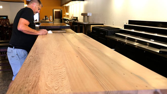 Randy Cunzenheim stains a table top in preparation for the reopening of Theo's restaurant at 24 N. Main St.